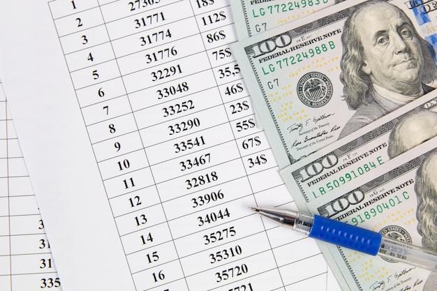 Concetto di affari. grafici finanziari, dollari usa e penna