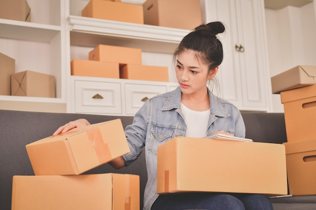 Concetto di affari i giovani asiatici stanno preparando i loro pacchi.