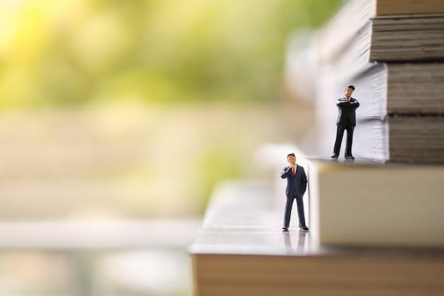 Concetto di affari, istruzione, conoscenza e pianificazione. due figure miniatura della gente dell'uomo d'affari che stanno sulla pila di libri con lo spazio della copia.