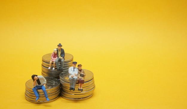 Concetto di affari. la gente seduta su una pila di monete d'argento.