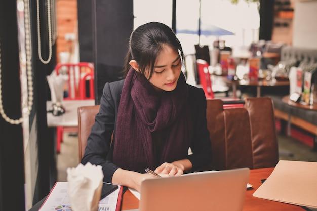 Concetto di affari la giovane donna di affari asiatica sta funzionando felicemente.