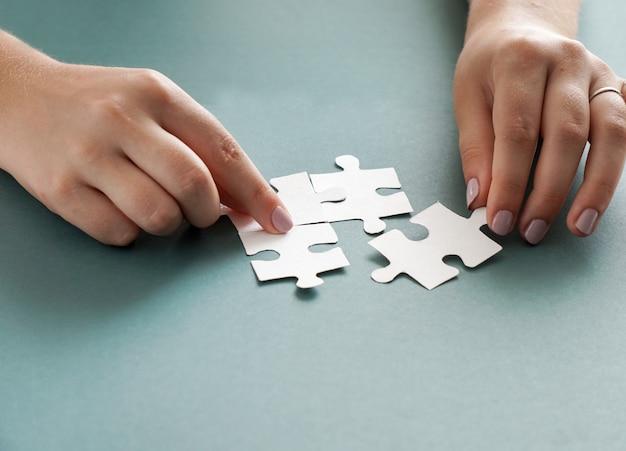 Concetto di affari, mani di donne che tengono i pezzi del puzzle bianco