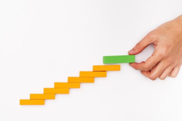 Concetto di affari per il processo di successo della crescita, blocco di legno della pila della mano come scala di punto