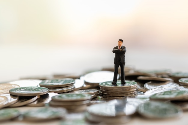Concetto di affari, pianificazione, sicurezza, pensionamento e risparmio. chiuda su della figura miniatura dell'uomo d'affari che cammina sopra la pila di monete con lo spazio della copia.
