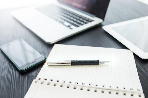 Concetto di affari, posto di lavoro dell'ufficio con il computer portatile sulla tavola di legno contro le finestre