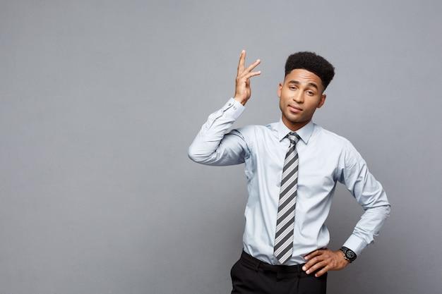 Concetto di affari - ritratto dell'uomo frustrato di affari afroamericano sollecitato su fondo grigio.