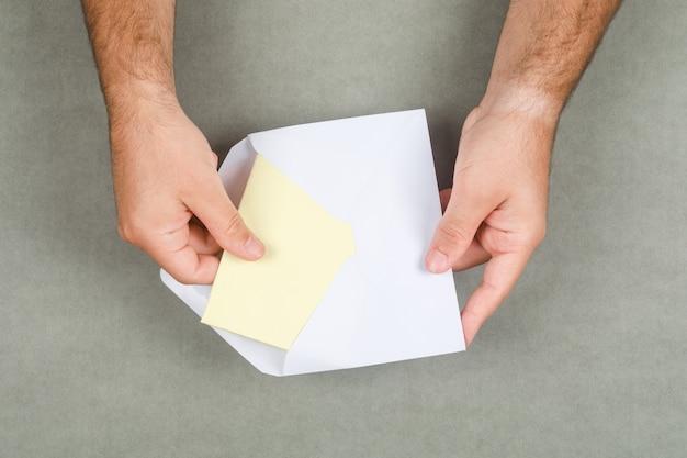 Concetto di affari sulla disposizione piana della superficie grigia. uomo che prende lettera dalla busta.