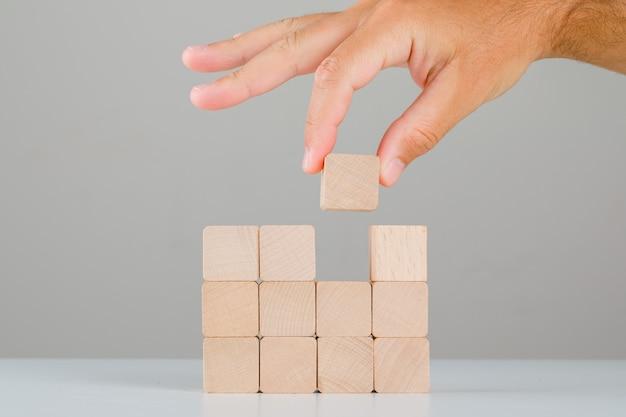 Concetto di affari sulla vista laterale della tavola bianca e grigia. mano tirando o posizionando il cubo di legno.