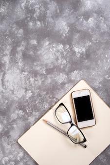 Concetto di affari - vista piana di disposizione dello smart phone, dei vetri, del blocco note e della penna con lo spazio della copia