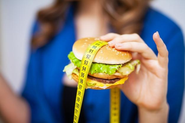 Concetto di alimentazione sana, hamburger con metro a nastro giallo