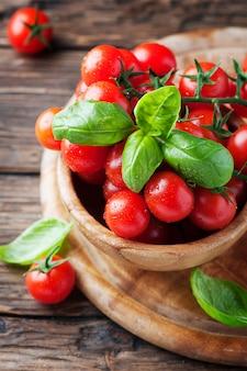Concetto di alimento sano vegetariano con il pomodoro e il basilico, fuoco selettivo