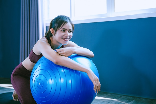 Concetto di allenamento; giovane donna sentirsi rilassarsi in classe di yoga
