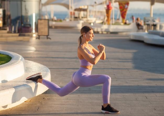 Concetto di allenamento mattutino. la donna adatta dei giovani in abiti sportivi che fanno gli affondi si esercita all'alba all'aperto