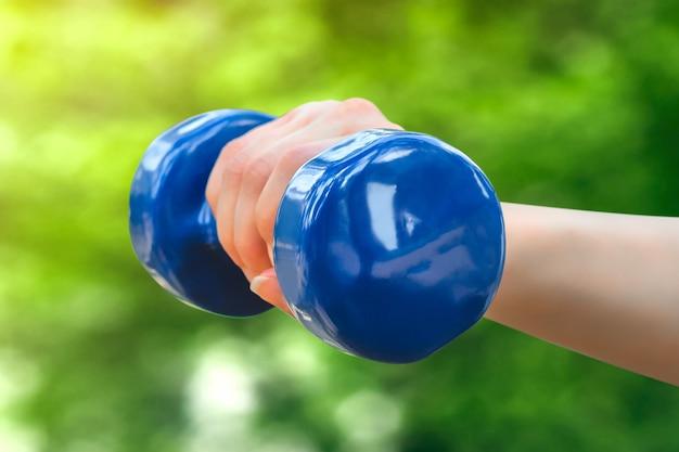 Concetto di allenamento sportivo la mano femminile sta tenendo un dumbbell blu