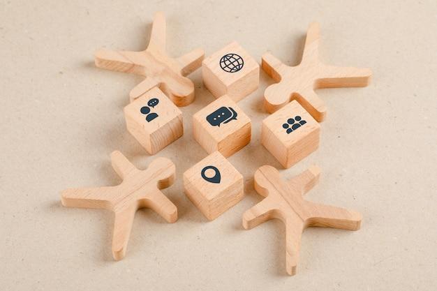 Concetto di allontanamento sociale con le icone sui cubi di legno, figure di legno vista dell'angolo alto.