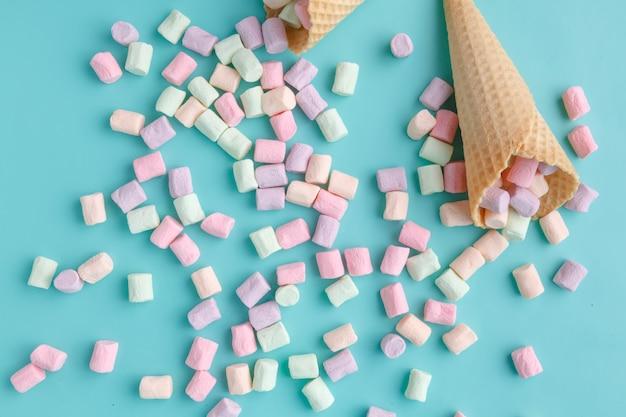 Concetto di amore del gelato, cono di cialda piatto sulla superficie blu