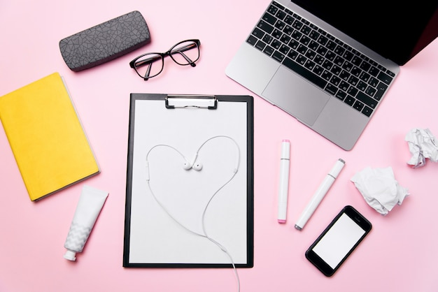 Concetto di amore dell'ufficio. scrivania da donna rosa con cuffie disposte come un cuore. posto di lavoro della donna con laptop, telefono con schermo bianco vuoto, crema, rossetto, occhiali e forniture.