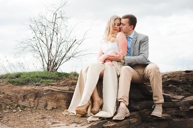 Concetto di amore, di romanticismo e della gente - giovani coppie felici che abbracciano seduta sull'orlo di una scogliera all'aperto.