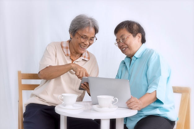 Concetto di amore; due donne senior che per mezzo della compressa e del computer portatile a casa