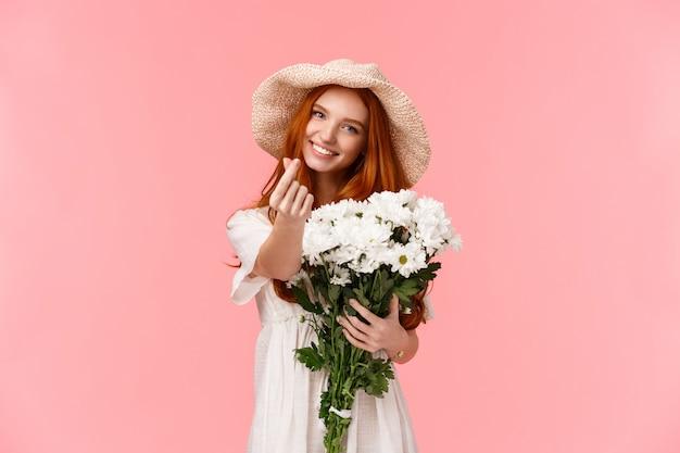 Concetto di amore, relazione e celebrazione. carina e sciocca ragazza carismatica rossa esprime cura e tenerezza, riceve bellissimi fiori bouquet, tenendolo e facendo un gesto coreano cuore