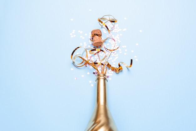 Concetto di apertura di una costosa bottiglia di champagne dorata dedicata alla celebrazione