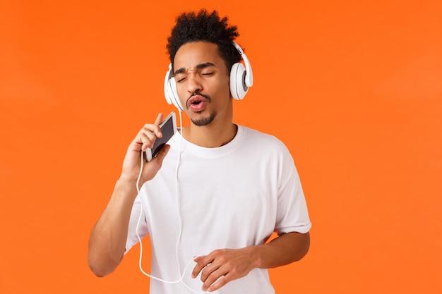 Concetto di app, tecnologia e smartphone. maschio afroamericano allegro spensierato che gioca il gioco di karaoke, applicazione, cantando nel microfono mobile, indossando le cuffie, ascolta la musica