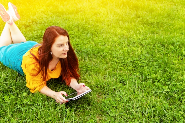 Concetto di apprendimento giovane donna che per mezzo dell'erba mettente su all'aperto della compressa
