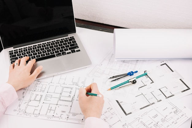 Concetto di architettura con piano di costruzione e laptop