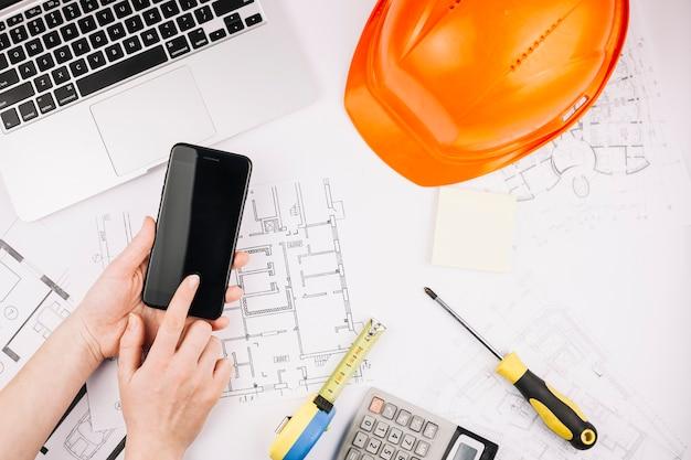 Concetto di architettura con piano di costruzione e smartphone