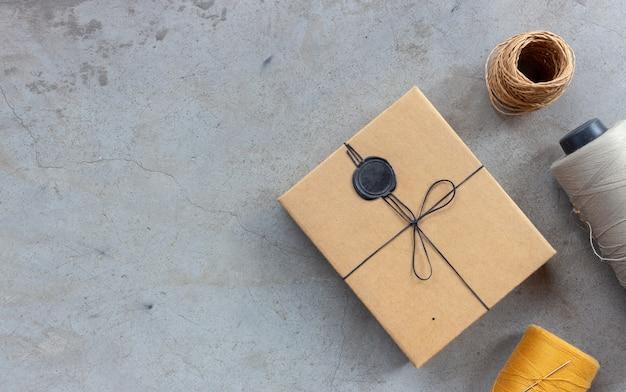 Concetto di artigianato e fai-da-te. fili per cucire e scatole per regali sul pavimento di cemento. vista dall'alto