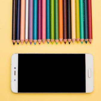 Concetto di artista incantevole con matite colorate e smartphone