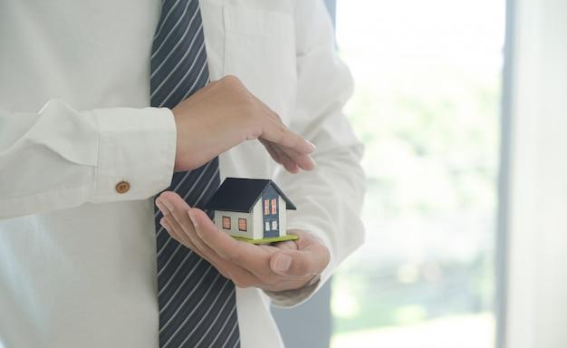 Concetto di assicurazione di proprietà: l'agente di assicurazione tiene in mano un modello di casa che mostra il simbolo dell'assicurazione casa.