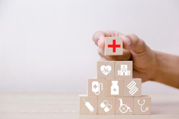 Concetto di assicurazione sanitaria, mano che organizza il blocco di legno che impila con l'assistenza sanitaria dell'icona medica, per salute