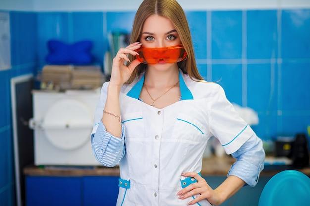 Concetto di assistenza sanitaria. bella ragazza nelle camice che tengono gli occhiali di protezione arancio.