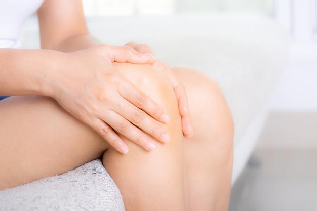 Concetto di assistenza sanitaria. donna che soffre dal dolore al ginocchio, primo piano