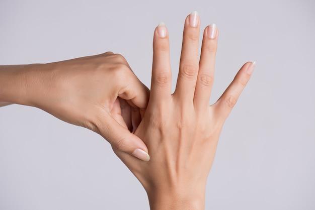 Concetto di assistenza sanitaria e medica. donna che massaggia la sua mano dolorosa