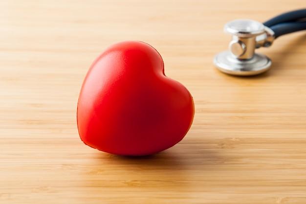 Concetto di assistenza sanitaria e medica. stetoscopio e cuore rosso sul tavolo di legno.