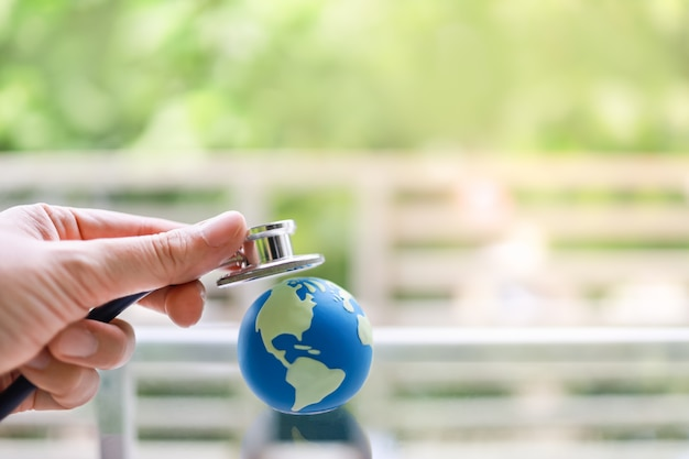 Concetto di assistenza sanitaria globale. primo piano della mano dell'uomo che tiene lo stetoscopio e posato sulla mini palla del mondo.