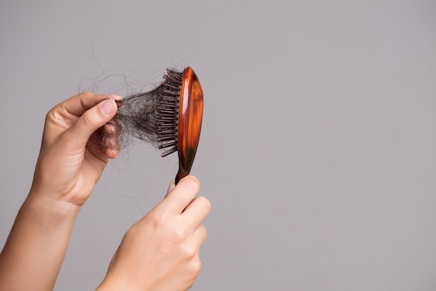 Concetto di assistenza sanitaria. la donna mostra una lunga perdita di capelli e tira i capelli dal pennello.