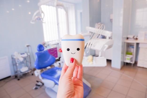 Concetto di assistenza sanitaria, stomatologia e medicina modello di dente del dente con viso carino modello ortodontico e strumento del dentista - modello di dimostrazione dei denti delle varianti della staffa ortodontica o del tutore.
