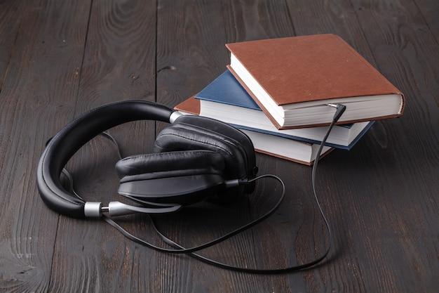 Concetto di audiolibro con cuffia e tascabile sul tavolo