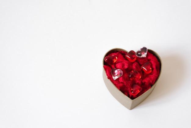 Concetto di auguri di san valentino. confezione regalo artigianale a forma di cuore con cuori di vetro su un bianco