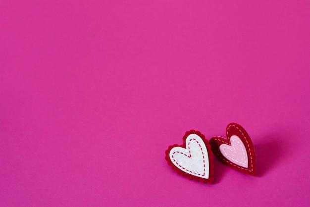 Concetto di auguri di san valentino. cuori creativi su un rosa brillante o cremisi