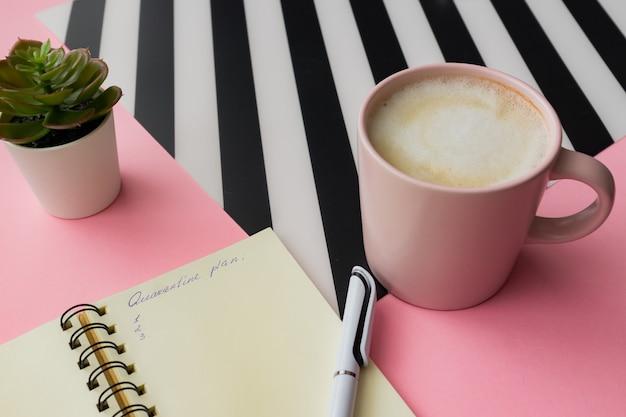 Concetto di autoisolamento. apri il blocco note con il piano di quarantena. tazza rosa di capuccino su una tavola