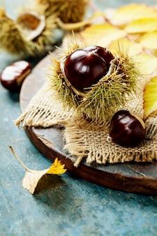Concetto di autunno con castagne e foglie su tavola di legno