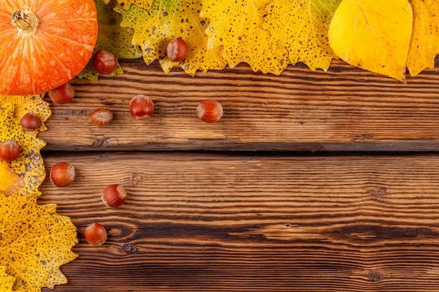 Concetto di autunno con copyspace: cornice di zucca con foglie e nocciole
