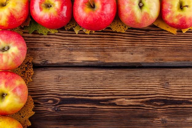 Concetto di autunno con copyspace: prodotti agricoli, mele rosse su legno