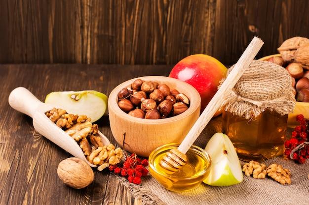 Concetto di autunno o raccolto: assortimento di noci, mele e miele.