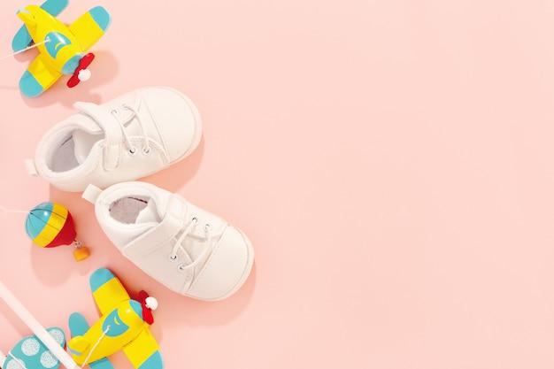 Concetto di bambino. accessori piatti con scarpe per bambini e aereo giocattolo in legno.