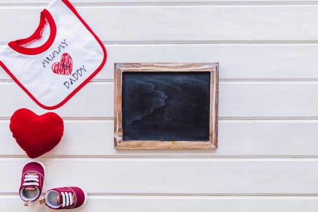 Concetto di bambino con ardesia e bavaglio sulla superficie di legno